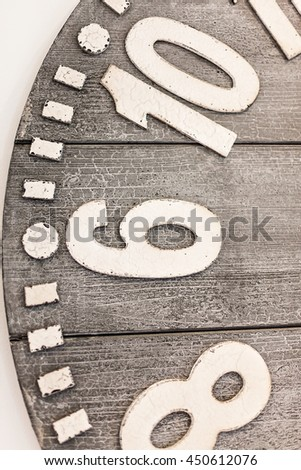 Closeup of a wooden watch half with embossed metal or 3d material numbers on the old and rough wooden face - stock photo