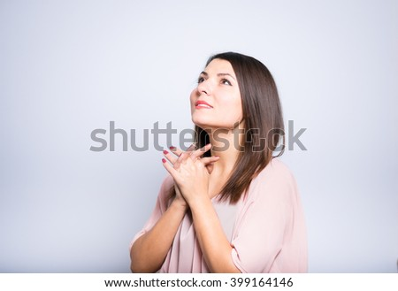 closeup of a young beautiful woman begs, pray - stock photo