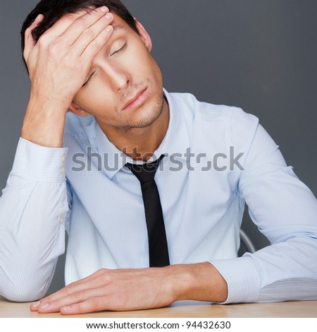 Closeup of a young business man having a stress. Headache. Against gray background - stock photo