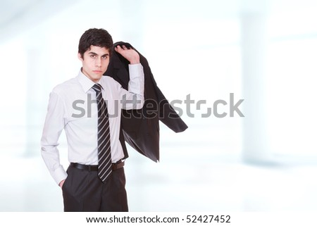 Closeup of a young business man standing in a light and mordern background.