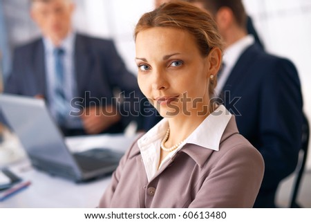 Closeup of a young businesswoman with her colleagues at the background. - stock photo