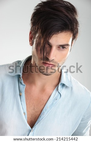 Closeup of a young casual man in blue shirt, on gray background - stock photo