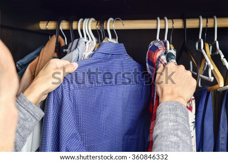 closeup of a young caucasian man choosing a shirt from a clothes rack - stock photo