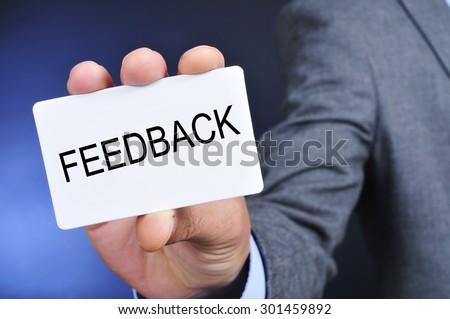 closeup of a young caucasian man in suit showing a signboard with the word feedback written in it
