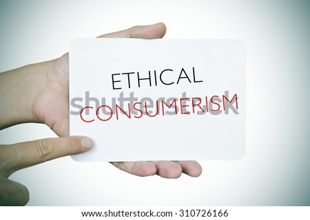 closeup of a young caucasian man pointing his finger at a signboard with the text ethical consumerism, slight vignette added - stock photo