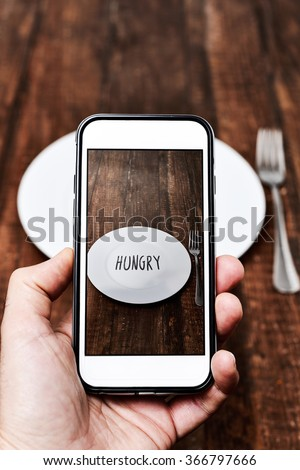 closeup of a young caucasian man taking a picture with his smartphone of a plate with the word hungry written in it, placed on a wooden table - stock photo