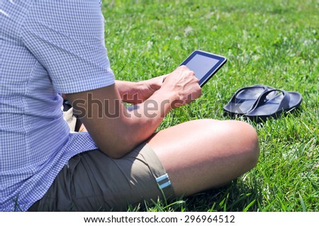 closeup of a young caucasian man using a tablet computer in a park or a garden - stock photo