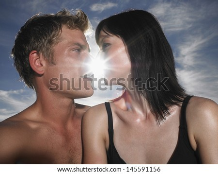 Closeup of a young couple about to kiss with sun behind - stock photo