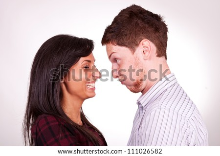 closeup of a young couple - man amusing his girlfriend, goofing around - stock photo