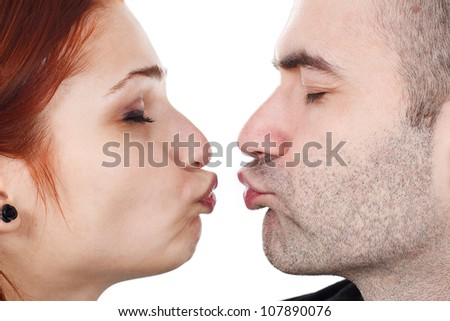 Closeup of a young couple, their lips getting close to each other, eyes closed - isolated on white