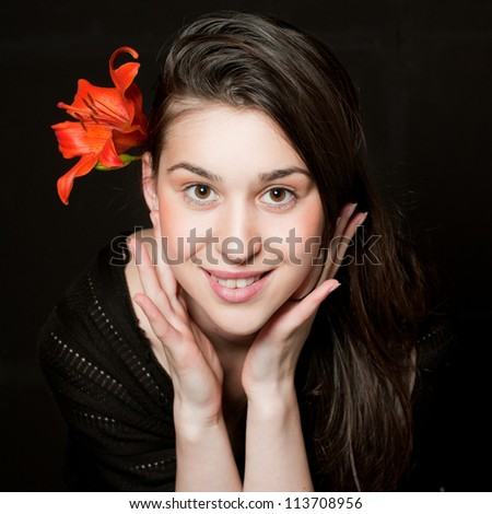 Closeup of a young fresh and tenderness woman with flower in hair - stock photo