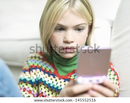 Closeup of a young girl playing handheld video game on sofa - stock photo