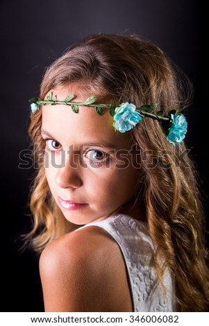 Closeup of a young girl with long hair and flower tiara posing with a sober look on a black background - stock photo