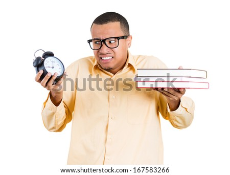 Closeup of a young handsome man, wearing big glasses, holding books and clock, anxious in anticipation of finals test, isolated on white background. Negative facial expressions, feelings, emotion - stock photo