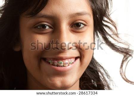 Closeup of a young hispanic girl wearing braces.  Smiling at the camera. White background - stock photo