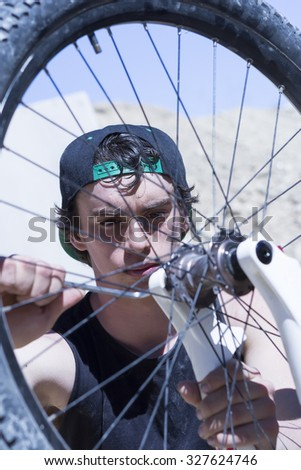 closeup of a young man BMX biker fixing the wheel of his bike on a BMX session in the mountain - focus on the right eye - stock photo