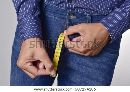 closeup of a young man holding a piece of measuring tape that is popping up from the fly of his jeans, depicting the normal range of the penis