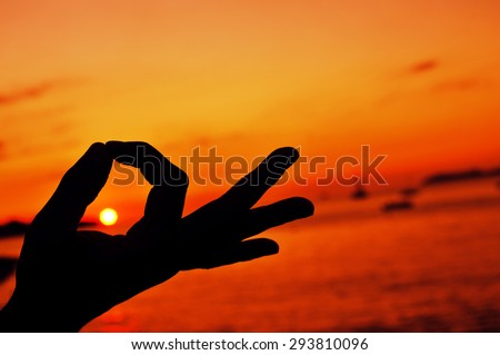 closeup of a young man meditating with his hands in gyan mudra at sunset - stock photo