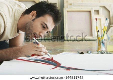 Closeup of a young man painting on canvas on studio floor - stock photo