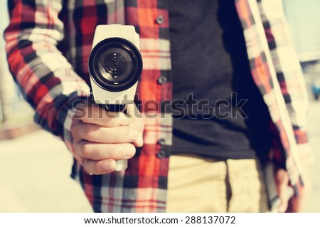 closeup of a young man pointing a Super 8 camera at the observer like it was a gun - stock photo