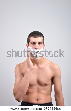 Closeup of a young man preparing to shave, he puts foam on his cheek - stock photo