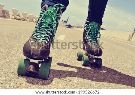 closeup of a young man roller skating, with a cross-processed effect - stock photo