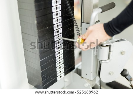 Closeup of a young man selecting the weight while working out