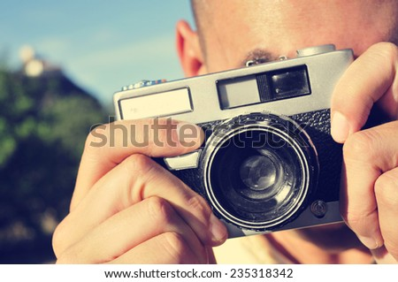 closeup of a young man taking a picture with an old camera outdoors - stock photo