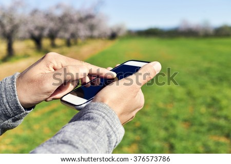 closeup of a young man using a smartphone in a natural landscape, with a grove of almond trees in full bloom in the background - stock photo