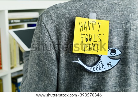 closeup of a young man with a paper fish and a note with the text happy fools day attached with tape to his back - stock photo