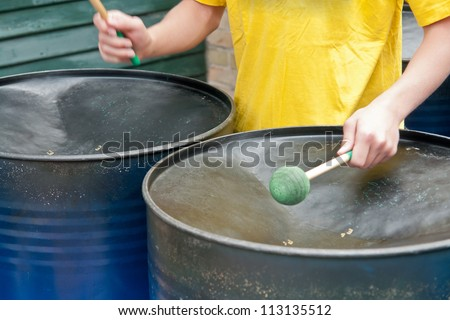 Closeup of a young musician playing Caribbean style metal steel drums - stock photo