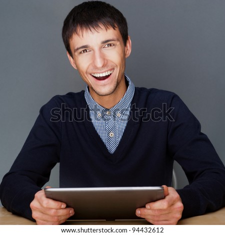 Closeup of a young smiling business man sitting at his office against gray wall and using his modern tablet pc to do his work - stock photo