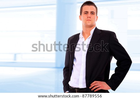 Closeup of a young smiling business man standing in a light and mordern business environement