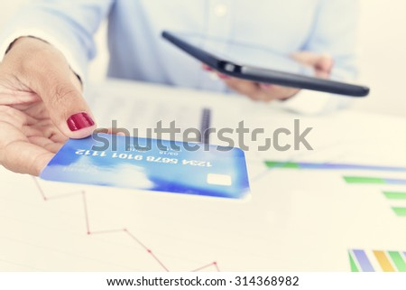 closeup of a young woman at her office with a credit card in one hand and a tablet computer in the other hand