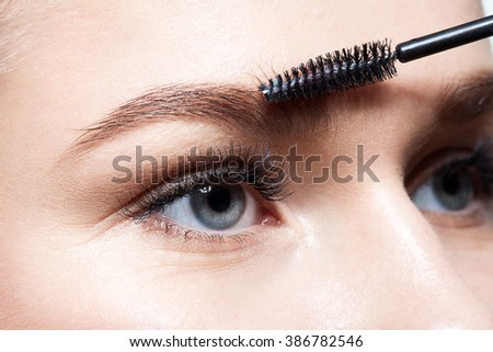 Closeup of a young woman doing makeup eyebrow brush - stock photo