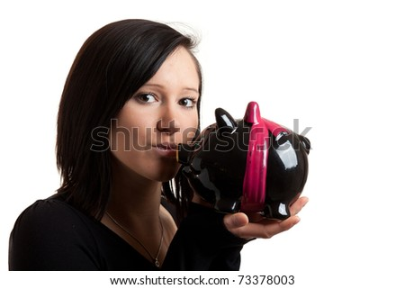 closeup of a young woman kissing a piggy bank isolated on white - stock photo