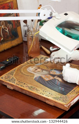 Closeup of accurate restoration of old icon with  filling knife at workshop - stock photo