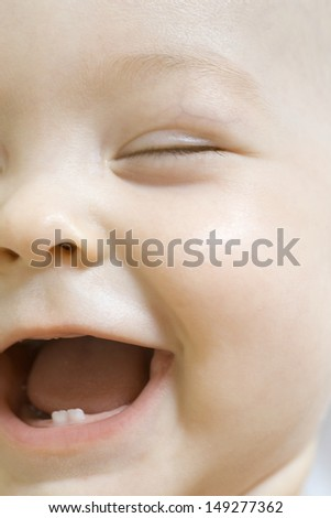 Closeup of adorable baby boy laughing with eyes closed - stock photo