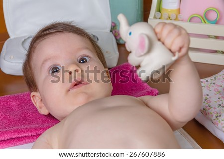 Closeup of adorable baby lying playing with a toy rubber for children after the change of diaper - stock photo