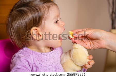 Closeup of adorable happy baby girl eating a slice of banana from the hand of her mother at home - stock photo