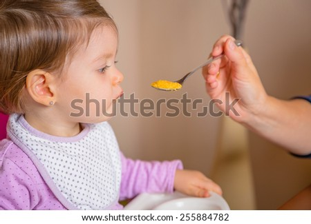Closeup of adorable happy baby sitting in a feeding chair eating puree from a spoon in the hand of her mother at home - stock photo
