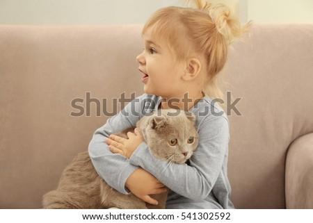 Closeup of adorable little girl embracing cute cat on grey sofa