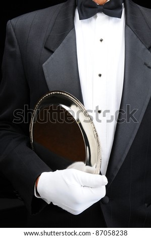 Closeup of af butler with a silver tray under his arm. Man is wearing a tuxedo and white gloves showing torso only in vertical format.