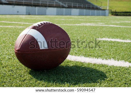 Closeup of American football on field with yard lines. - stock photo