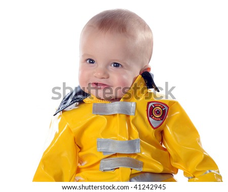 Closeup of an adorable baby boy wearing a fireman's suit.  Isolated on white. - stock photo