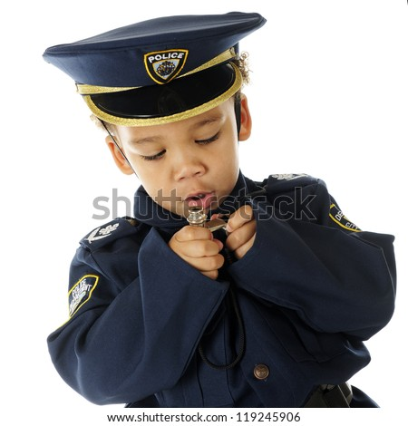 Closeup of an adorable preschool policeman in full uniform examining his two silver whistles.  On a white background.