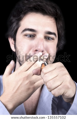 Closeup of an adult man (30 years old), looking extremely delighted as he is about to start smoking a marijuana spliff. Isolated on black background. - stock photo