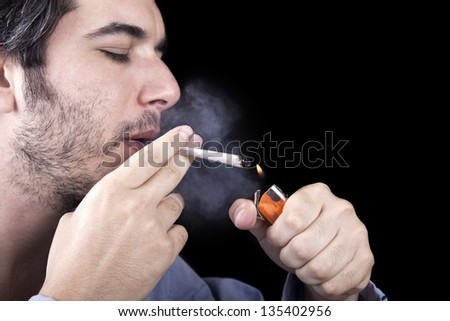 Closeup of an adult man (30 years old) with his profile to the camera concentrated on lighting a marijuana spliff (aka reefer; joint) with a simple lighter. Isolated on black background.