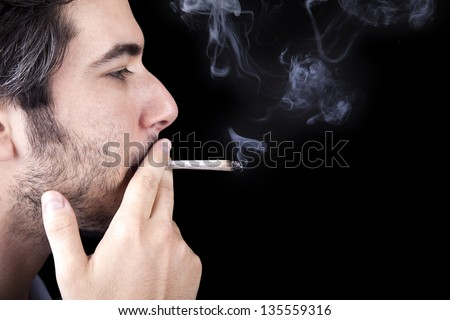 Closeup of an adult man (30 years old) with his profile to the camera. He appears to be quite a bum, concentrated in smoking a marijuana spliff (aka reefer; joint). Isolated on black background. - stock photo