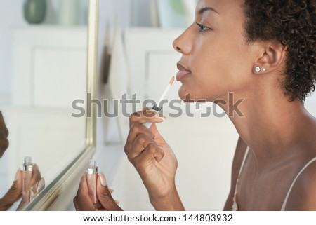 Closeup of an African American woman applying lip gloss in mirror at home - stock photo